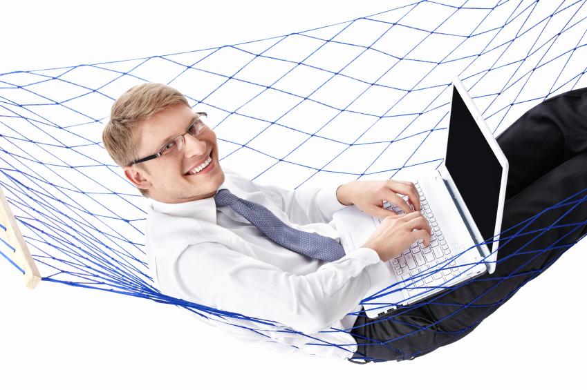 Man die met laptop in een hangmat ligt